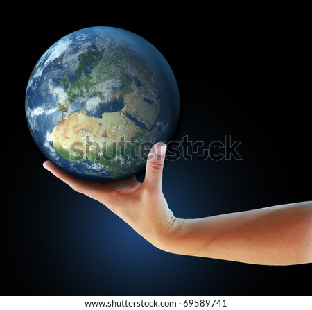 Hand holding realistic small globe symbolizing environmental care, facing Europe