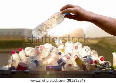 Hand holding recyclable plastic  bottle in garbage bin with sunset light - stock photo