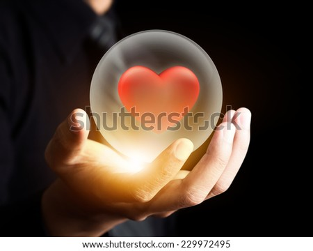 Hand holding red heart in crystal ball,Insurance concept - stock photo