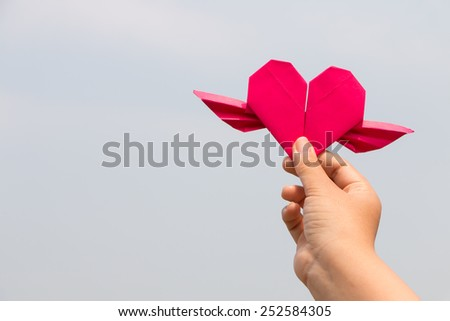 hand holding red paper heart - stock photo