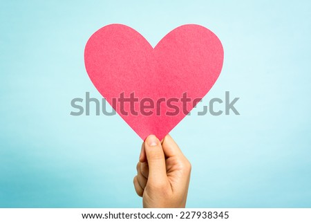 Hand holding red paper love heart shape on blue background. Love concept. - stock photo
