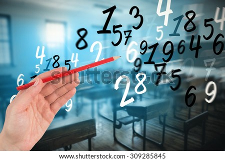 Hand holding red pencil against empty classroom - stock photo