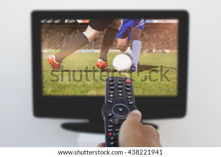 Hand holding remote and changing channel against football players tackling for the ball on pitch