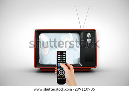 Hand holding remote control against white background with vignette - stock photo