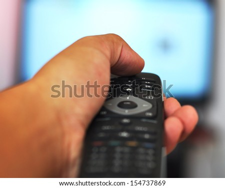Hand holding remote controller with tv in the background - stock photo