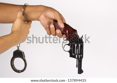Hand holding revolver and handcuffs on a white background - stock photo