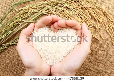 Hand holding rice forming heart in palm