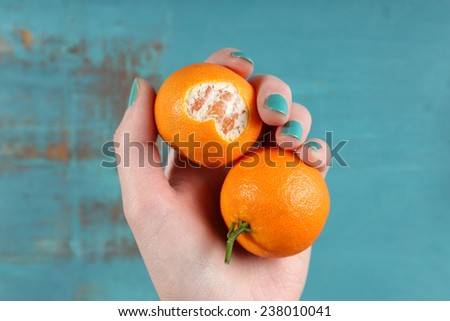 Hand holding ripe tangerines, close up - stock photo