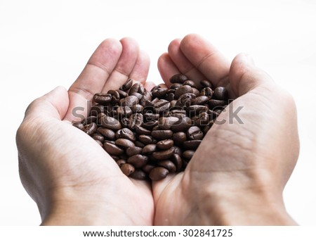 Hand holding roasted coffee beans - stock photo