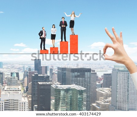 Hand holding rope with people on business bar graph with New York city in the background - stock photo
