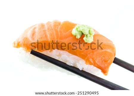Hand holding salmon sushi and wasabi with chopsticks on white ba - stock photo