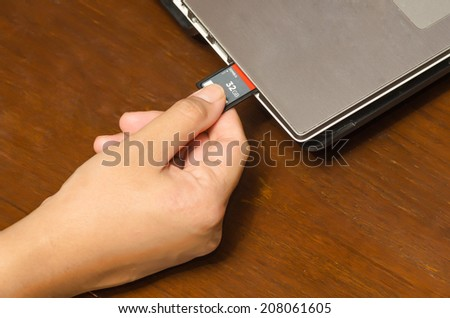 hand holding SD card insert to notebook computer - stock photo