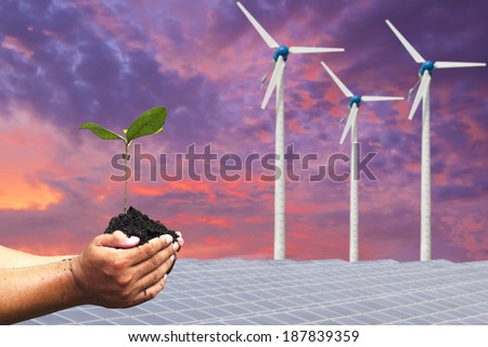Hand holding seedling background solar cells and wind turbines. natural Energy - stock photo