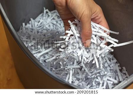 Hand holding shredded paper strips in a basket shredders - stock photo
