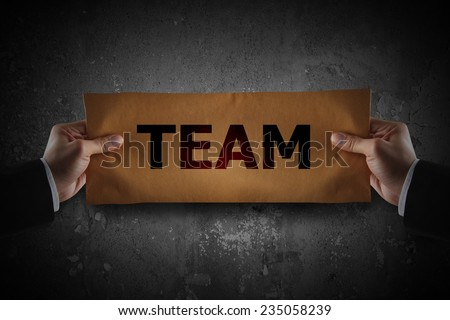 Hand holding sign team on paper - stock photo