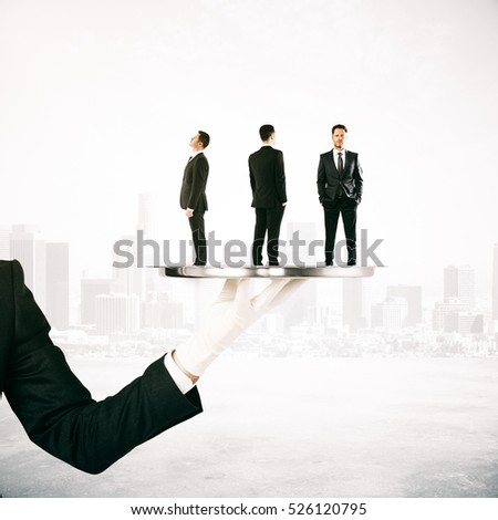 Hand holding silver tray with three tiny businessmen on blue background. HR concept