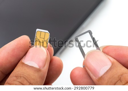 Hand holding sim card ans sim card tray - stock photo