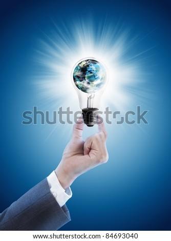 Hand holding single light bulb with globe - stock photo