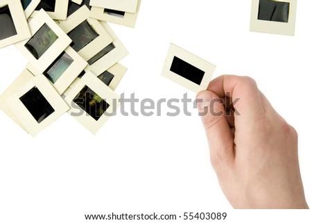 Hand, holding slide and pile of slides on white background - stock photo
