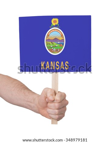 Hand holding small card, isolated on white - Flag of Kansas - stock photo