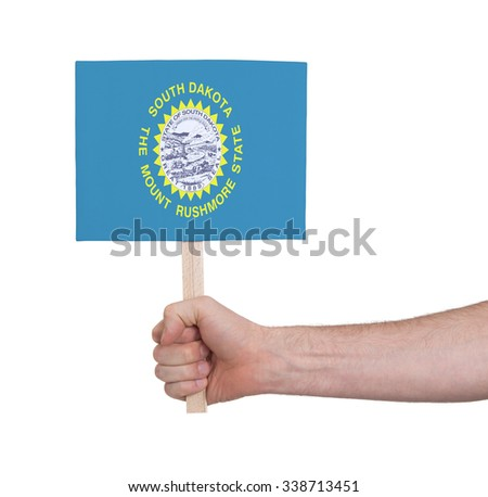Hand holding small card, isolated on white - Flag of South Dakota - stock photo