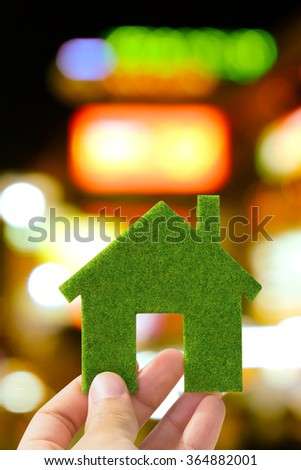 Hand holding small green eco house icon with defocused city night light background, green energy concept - stock photo