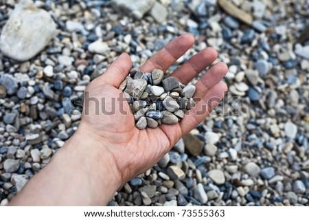 Hand holding small stones - stock photo