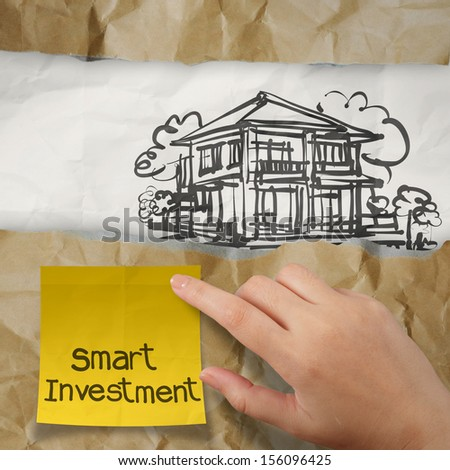 hand holding smart investment sticky note with  house on wrinkled paper as concept - stock photo