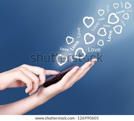 Hand holding smart mobile phone, heart icon and love text flying away
