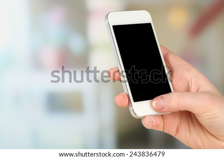Hand holding smart mobile phone on light blurred background - stock photo