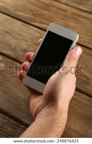 Hand holding smart mobile phone on wooden table background - stock photo