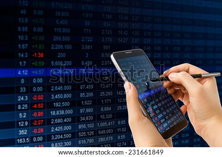 Hand holding smart phone checking financial stats on screen.  - stock photo