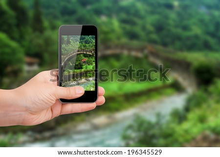 Hand holding smart phone focused on green landscape of plateau on blurry background. - stock photo