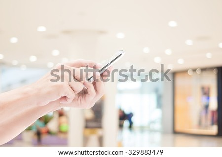 Hand holding smart phone on shopping mall backgrounds - stock photo