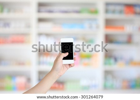 hand holding smart phone with blur some shelves of drug in the pharmacy drugstore - stock photo