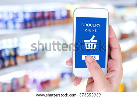 Hand holding smart phone with grocery shopping online on screen over blur supermarket background, retail business and technology concept - stock photo
