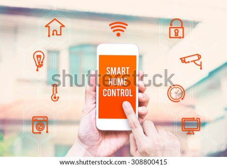 Hand holding smart phone with home control application with blur home background, Smart home concept. - stock photo
