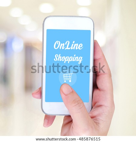 Hand holding smart phone with online shopping device on screen over blur store background, business and technology, digital marketing concept