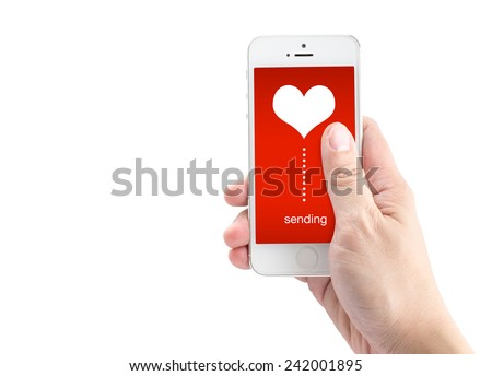 Hand holding smart phone with sending word and heart shape on screen on white background, Valentine's template - stock photo