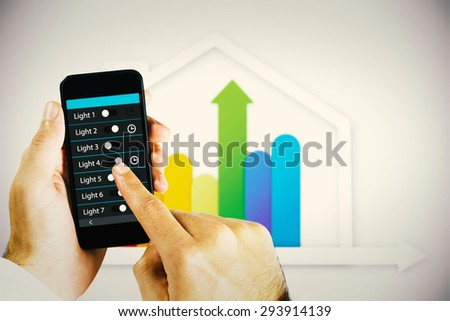 hand holding smartphone against house with colorful statistic - stock photo