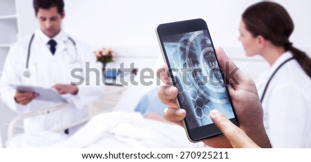 hand holding smartphone against medical interface on xray - stock photo