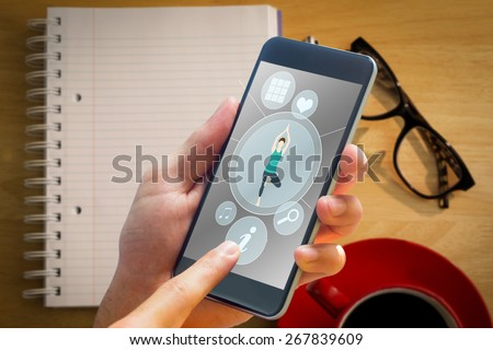 hand holding smartphone against overhead of notepad and pen - stock photo
