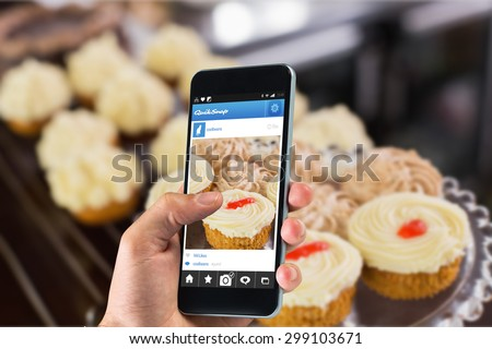 hand holding smartphone against variety of pastries at coffee shop - stock photo