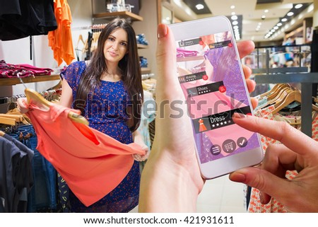 Hand holding smartphone against women looking at clothes - stock photo