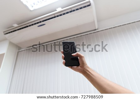 Hand holding smartphone as remote control setting air condition.