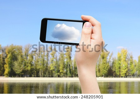 Hand holding smartphone, capturing cloud on clean sky - stock photo