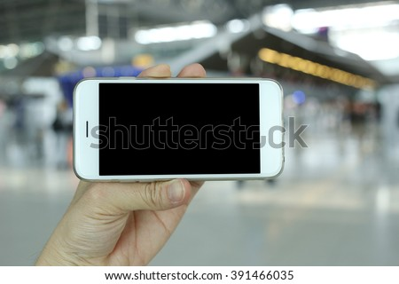 Hand holding smartphone landscape view with airport background - stock photo