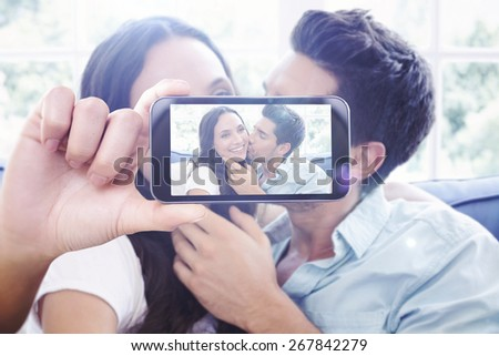Hand holding smartphone showing against attractive couple cuddling on the couch - stock photo