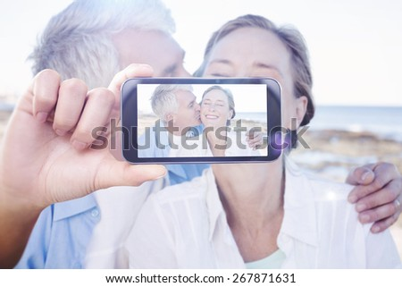 Hand holding smartphone showing against casual couple having fun by the sea - stock photo