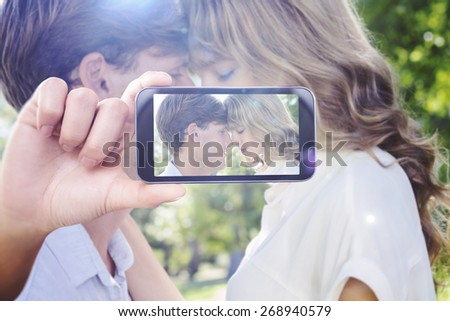 Hand holding smartphone showing against cute couple facing each other in the park - stock photo